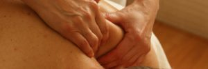 A massage therapist with two hands on a man's shoulder