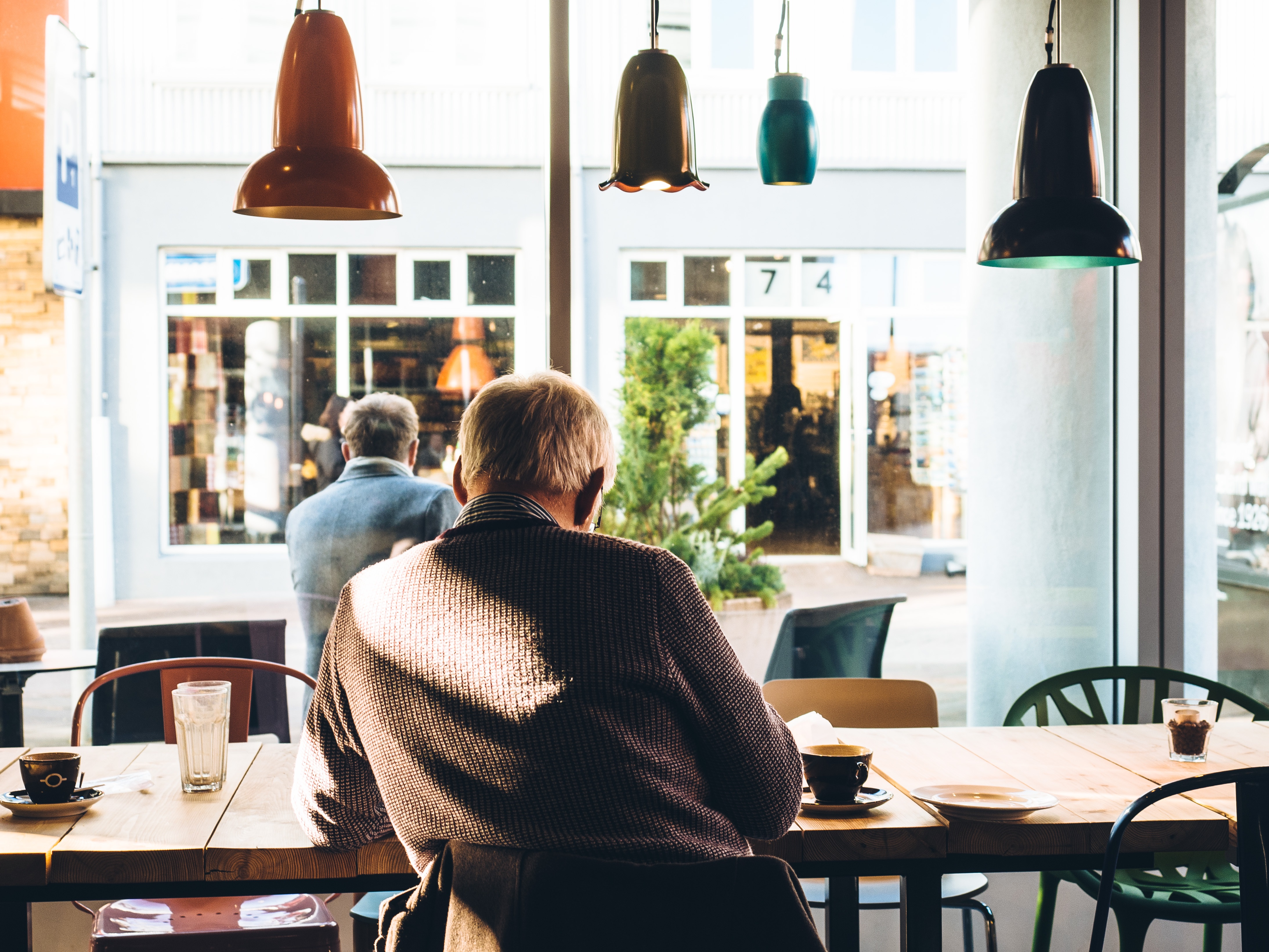 Man sitting in coffee shop with bad posture