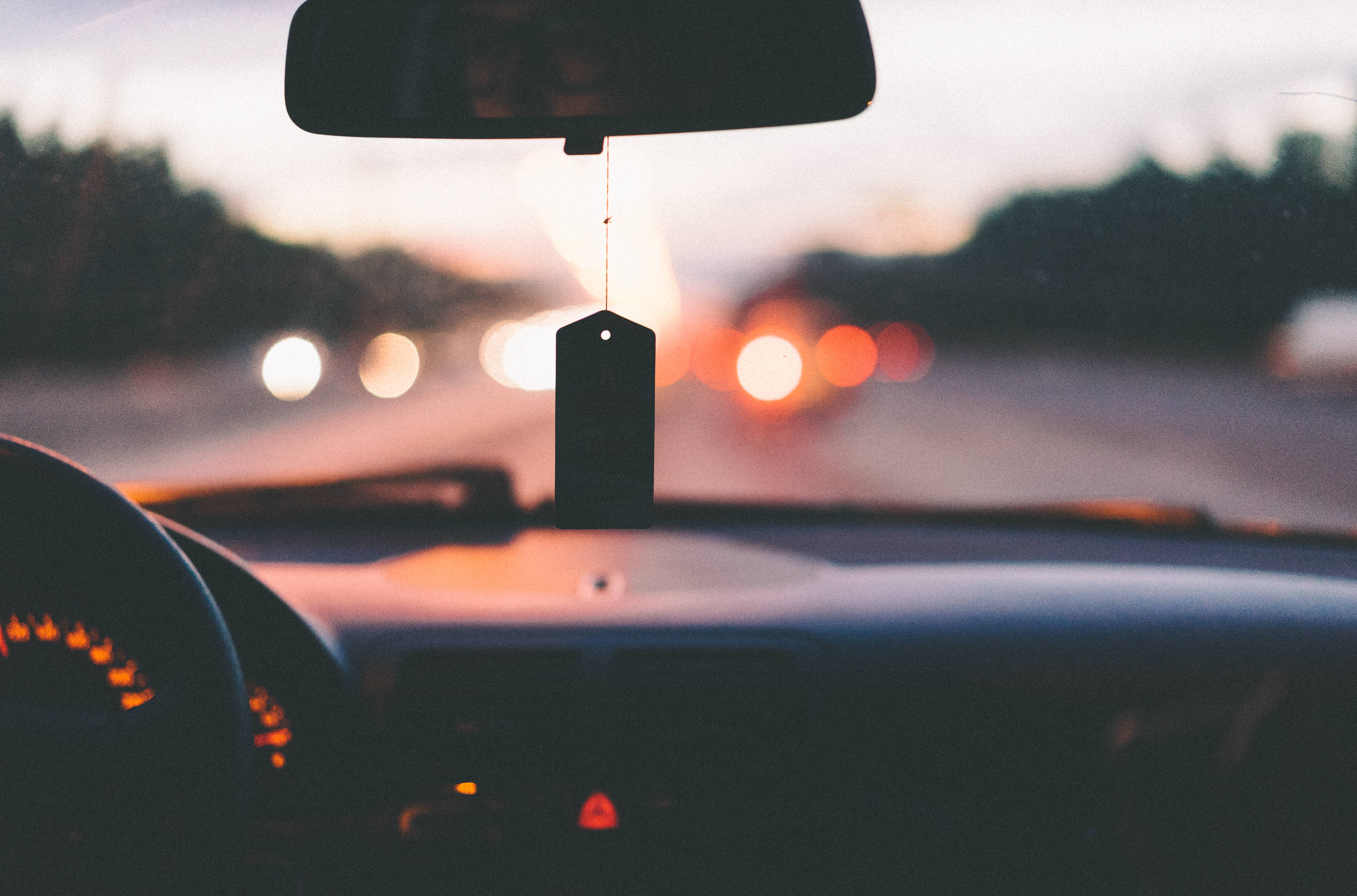 Car driving down highway at sunset