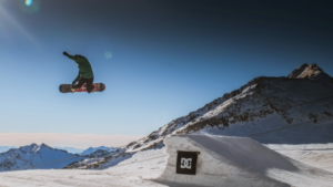 A snowboarder jumping off of a snow ramp